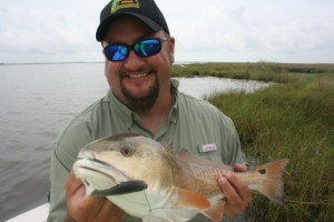 Shaun Haag showing off a keeper red fish caught with Captain Cuda Scheer - Sportsman's Paradise, Chauvin, La. uavin, La.